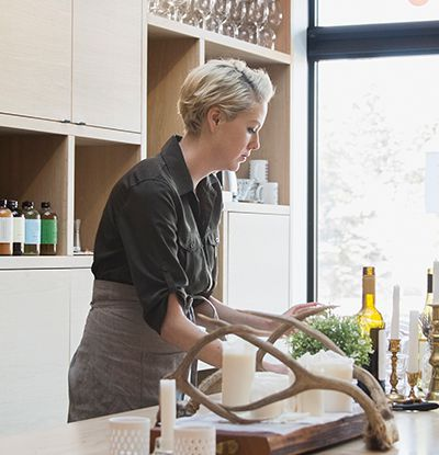 Woman at a kitchen working with herbs and drinks