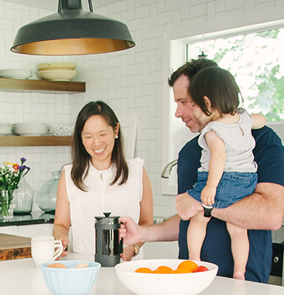 A couple with their young child in the kitchen as they make coffee
