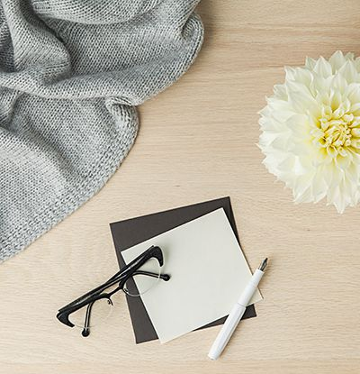 A scarf, white flower, note paper under a pen and glasses laid out on a wooden backdrop