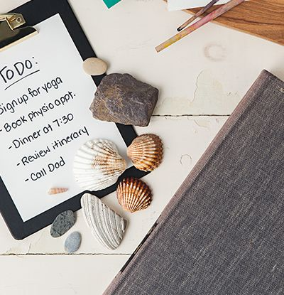 Seashells and rocks on a clipboard with a to-do list next to a cloth-bound book on a painted white wood backdrop