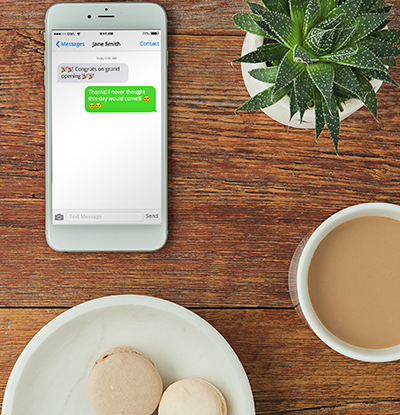 An iPhone, aloe vera plant, coffee, and macarons on a plate laid out on a wooden backdrop