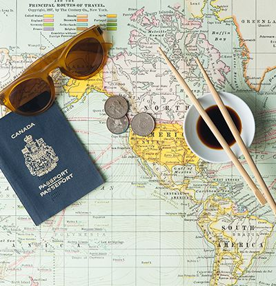 A passport, sunglasses, coins, and a bowl of soy sauce with chopsticks laid out on a map