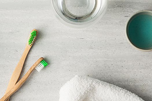 Two toothbrushes, a white towel and a cup on a bathroom counter.