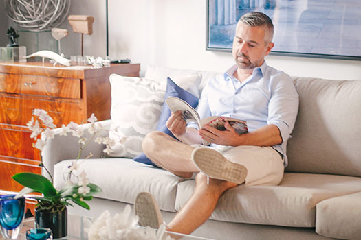 Man sitting on couch reading