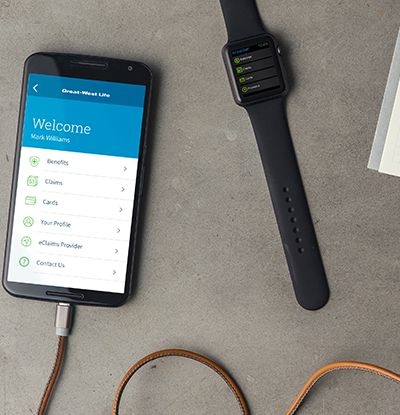 An Android smartphone plugged into a charger, next to a smartwatch on a smooth concrete backdrop